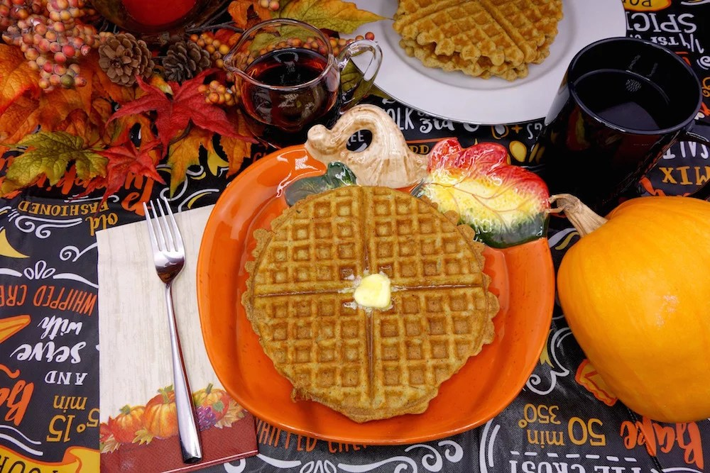 homemade Paleo pumpkin waffles on a pumpkin plate with melted grass-fed butter and surrounded by maple syrup, a fork and napkin, pumpkin, more Paleo pumpkin waffles, fall leaves, and coffee