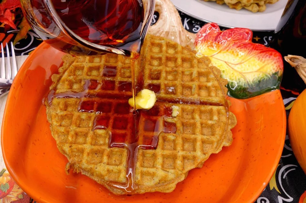 Maple syrup being drizzled over a pumpkin-inspired plate of hot, homemade Paleo Pumpkin Waffles