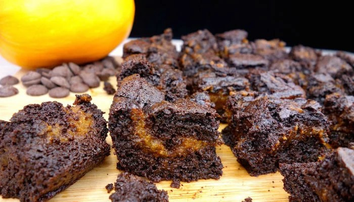 A close up picture of a homemade fudgy Paleo pumpkin swirl brownie on a cutting board, with other brownies in the background