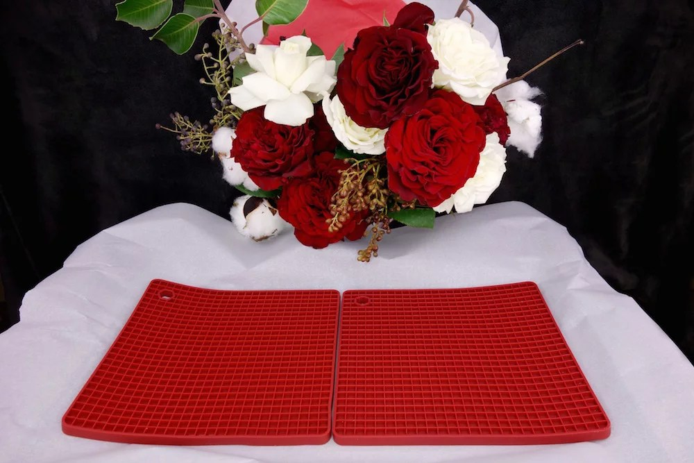 red chocolate chip molds on a parchment paper lined cookie sheet with a bouquet of red and white roses and cotton in the background