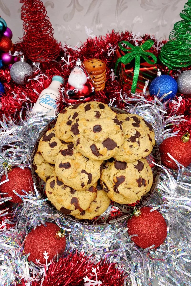 Homemade soft and chewy Paleo chocolate chip cookies stacked on a plate, surrounded by Christmas silver tinsel, red sparkly bulbs, and other Christmas ornaments