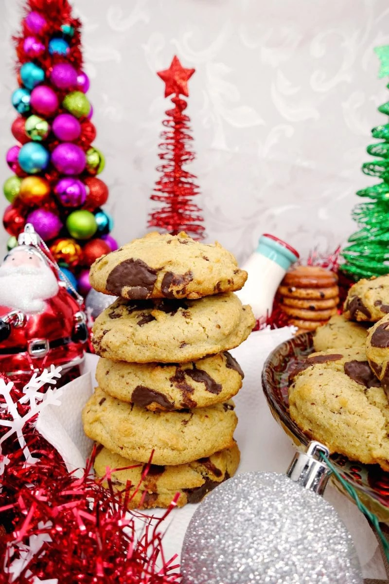 A stack of homemade soft and chewy Paleo chocolate chip cookies with christmas decorations of trees, santa, milk and cookies, and red tinsel surrounding them