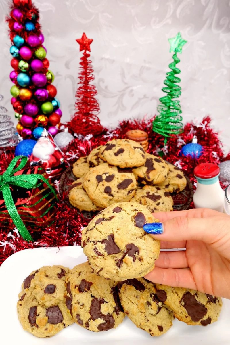 a hand holding a homemade soft and chewy Paleo chocolate chip cookie, with more cookies in the background with Christmas decorations