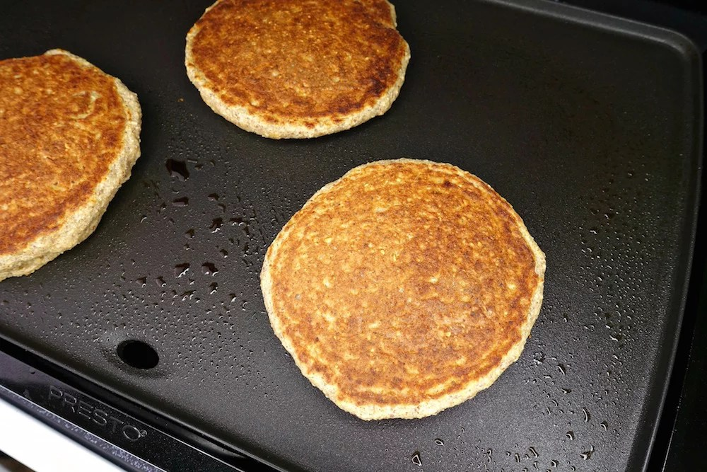 Homemade healthy gluten-free greek yogurt oat pancakes after being flipped on a black electric griddle