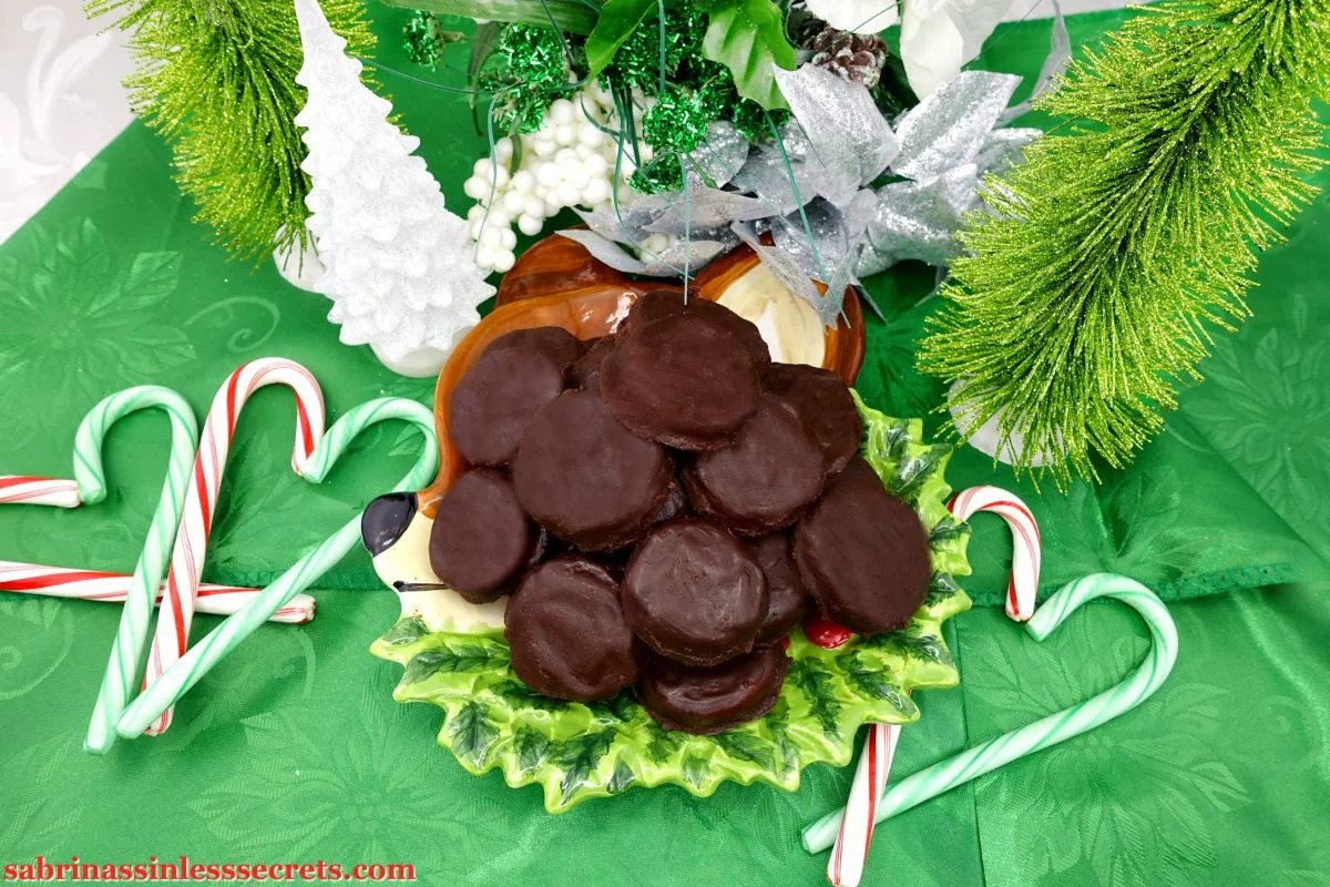 A mountain of Paleo Peppermint Patties on a reindeer plate on a green tablecloth with candy canes shaped in hearts, Christmas trees, and festive flowers