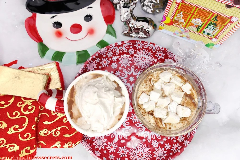 An overhead image of two mugs of Paleo hot chocolate, one with Paleo whipped cream on top and the other, Paleo marshmallows, sitting on top of a red and white snowflake plate with Christmas decor surrounding