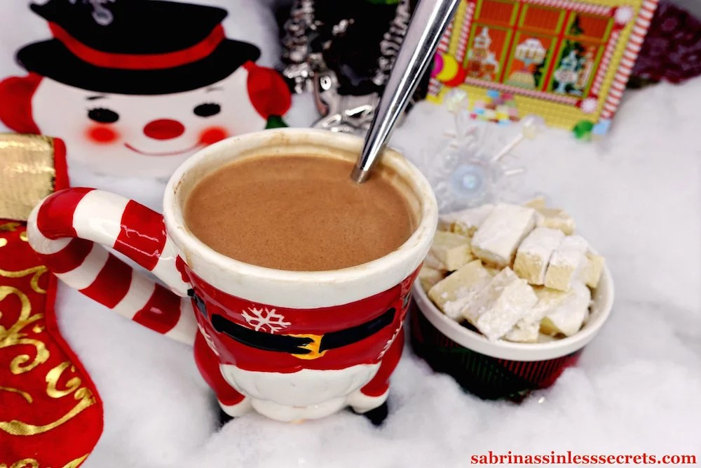 Paleo hot chocolate in a santa mug on top of fluffy snow with a cup of homemade Paleo marshals next to it, with additional Christmas decorations surrounding it