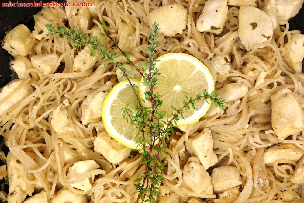 A close up of Lemon Thyme Honey Chicken with Angel Hair Pasta, garnished with lemon slices and lemon thyme sprigs
