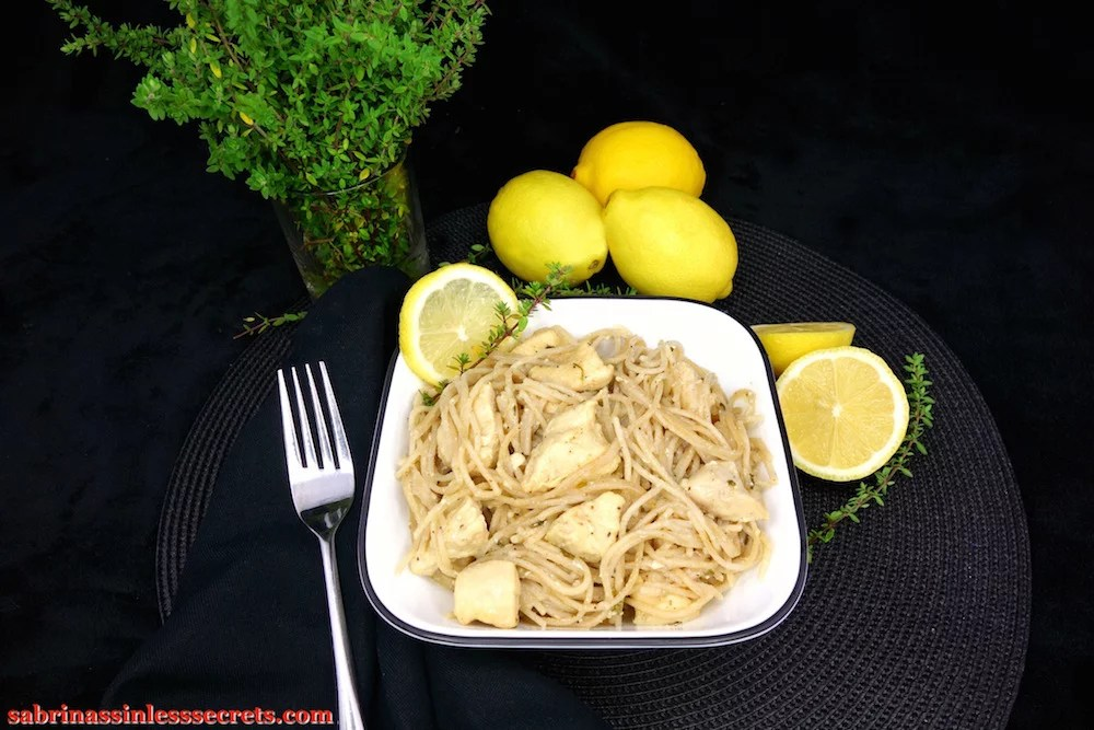 Lemon Thyme Honey Chicken with Angel Hair Pasta in a square white bowl, garnished with a lemon slice and lemon thyme spring, resting on a black background with a fork next to it and more lemon and lemon thyme