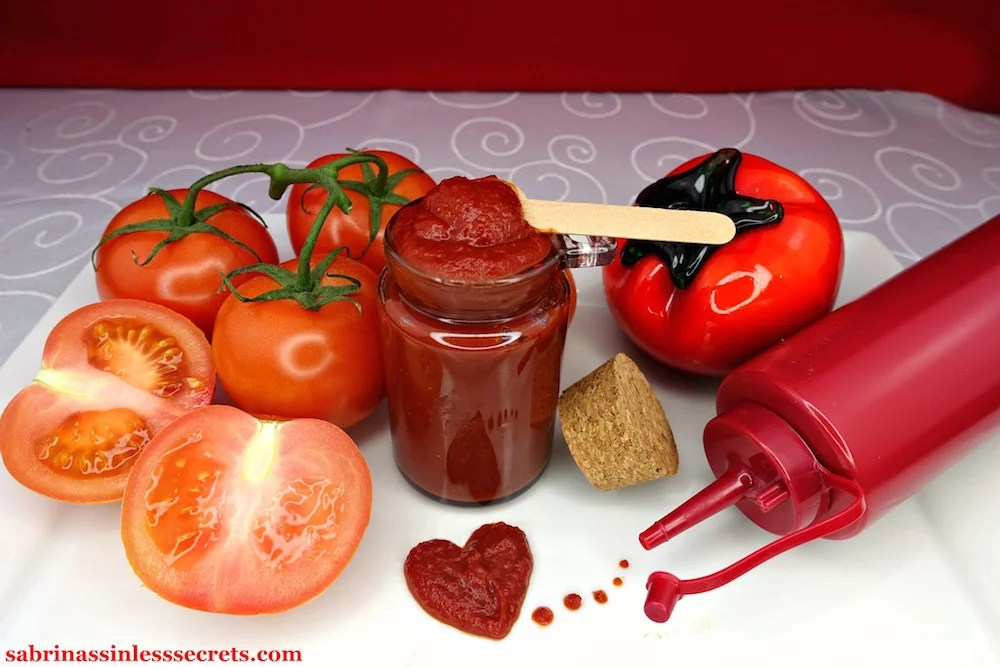 Homemade Quick & Easy Paleo Ketchup in a glass jar with a wooden spoon in it, with tomatoes on the vine surrounding it along with a glass tomato, red rubber ketchup bottle, and a heart formed from Paleo ketchup
