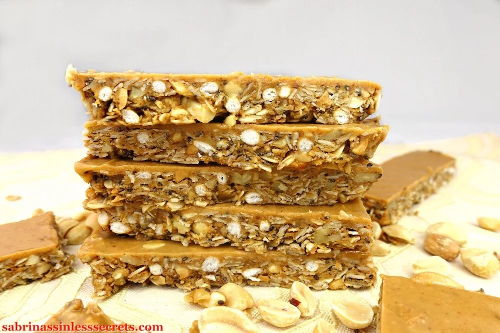 A stack of Gluten-Free Triple Peanut Butter Granola Bars with peanuts surrounding it