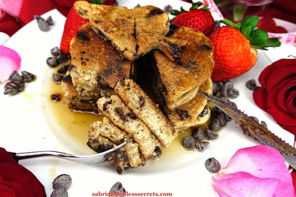 Homemade Paleo Dark Chocolate Chip Pancakes on a white plate cut in half with a generous bite on a fork resting in front of them, surrounded by maple syrup, chocolate chips, and fresh strawberries