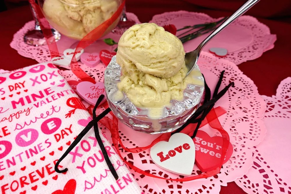 Two scoops of Creamy Vanilla Bean Paleo Ice Cream in a glass bowl with a spoon in it, sitting on a pink paper hearts, surrounded by fresh vanilla bean pods, hearts with messages, a white, pink, and red Valentine's Day towel, and a red diaphanous ribbon
