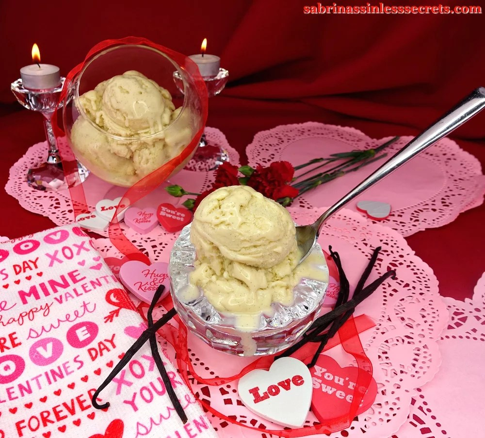 A chilled crystal bowl full of two scoops of Creamy Vanilla Bean Paleo Ice Cream with a spoon in it, with a glass stand-up bowl full of scoops of more ice cream in the background, resting atop pink paper hearts and encircled with red diaphanous ribbon, red carnations, and tea light candles atop crystal candles holders, and fresh vanilla beans