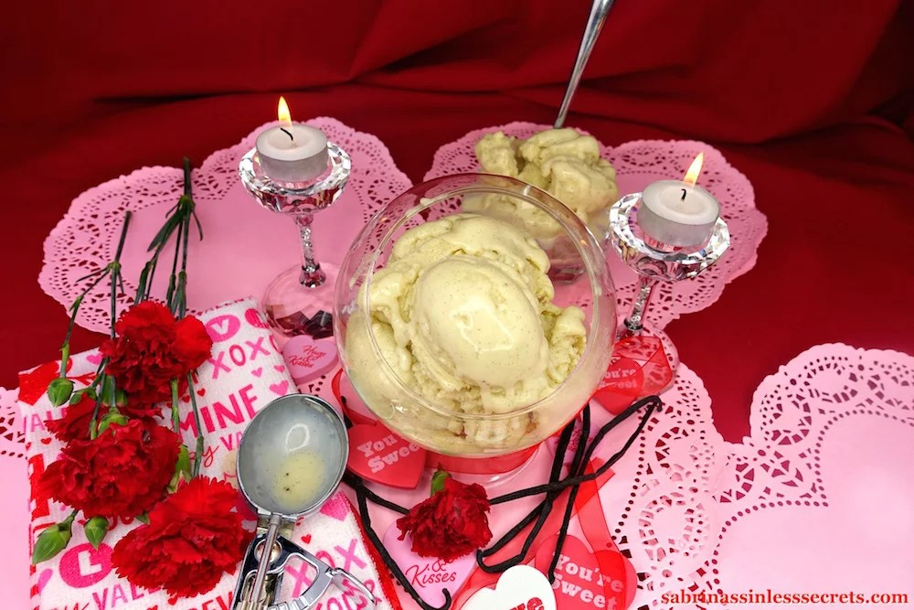 A bowl of Creamy Vanilla Bean Paleo Ice Cream scoops in a glass stand-up bowl, sitting atop pink paper hearts, surrounded by fresh vanilla beans, red carnations, heart messages, tea light candles atop crystal candle holders, and a used stainless steel ice cream scooper atop a Valentine's Day-inspired towel