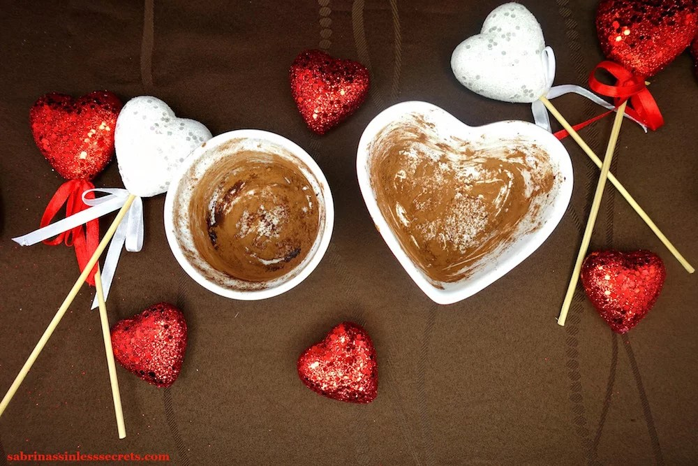 Two 6 oz. ramekins, one round and the other heart-shaped, dusted with raw cacao powder, sitting on a chocolate brown tablecloth with red and white sparkly hearts around them