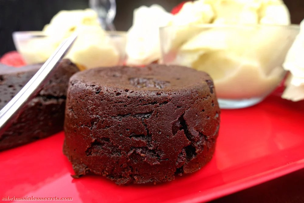 A round Dark Chocolate Paleo Lava Cake fresh out of the oven, sitting on a red heart-shaped plate with fresh Creamy Vanilla Bean Paleo Ice Cream in a bowl in the background