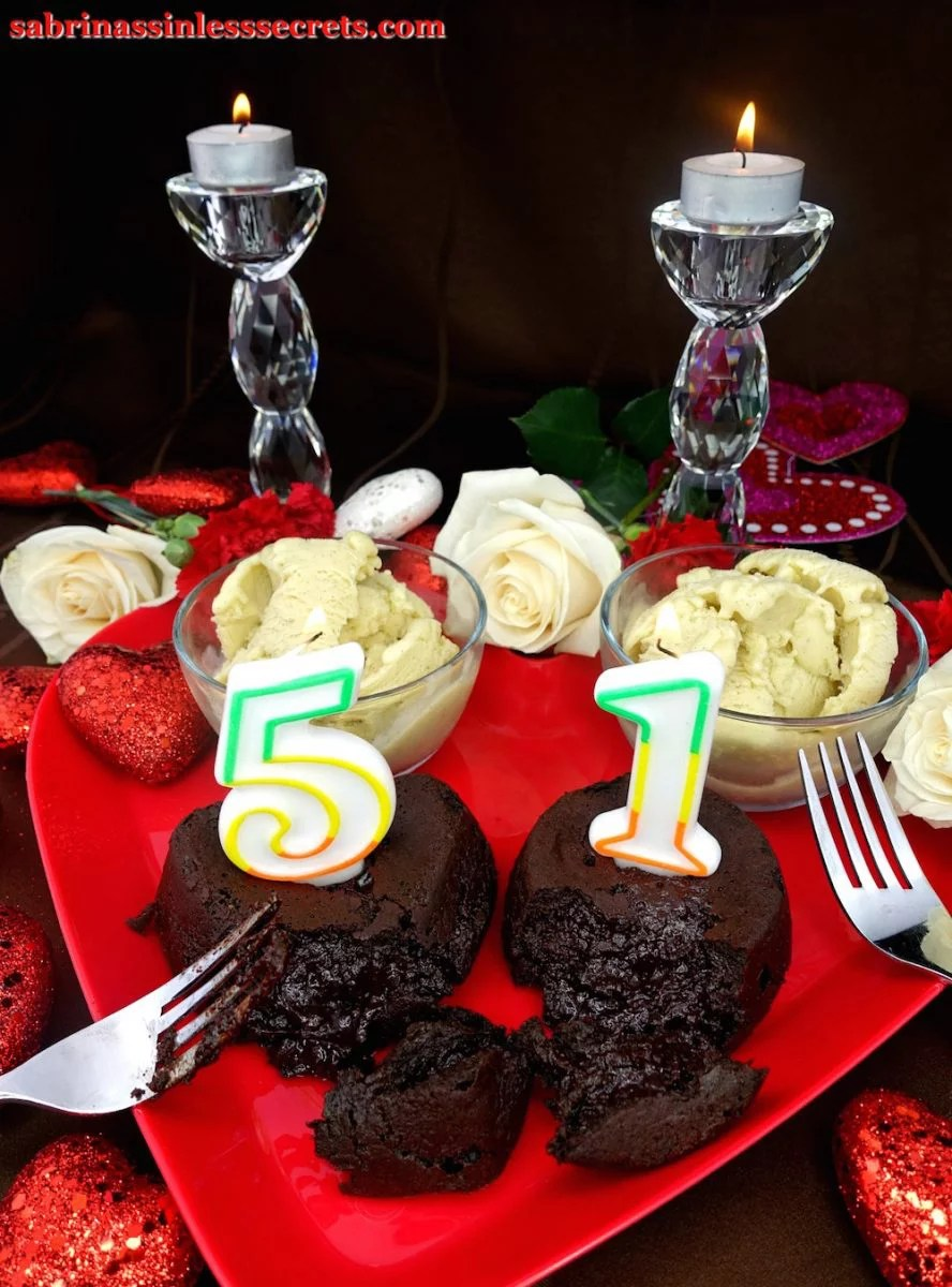 "Two Dark Chocolate Paleo Lava Cakes for Two with multicolored, lit ""5"" and ""1"" birthday candles atop them with two sides of Creamy Vanilla Bean Paleo Ice Cream, and two forks resting atop a red heart-shaped plate, with white roses, red carnations, red glittery hearts, and two crystal candle holders with white tea lights lit in the background."