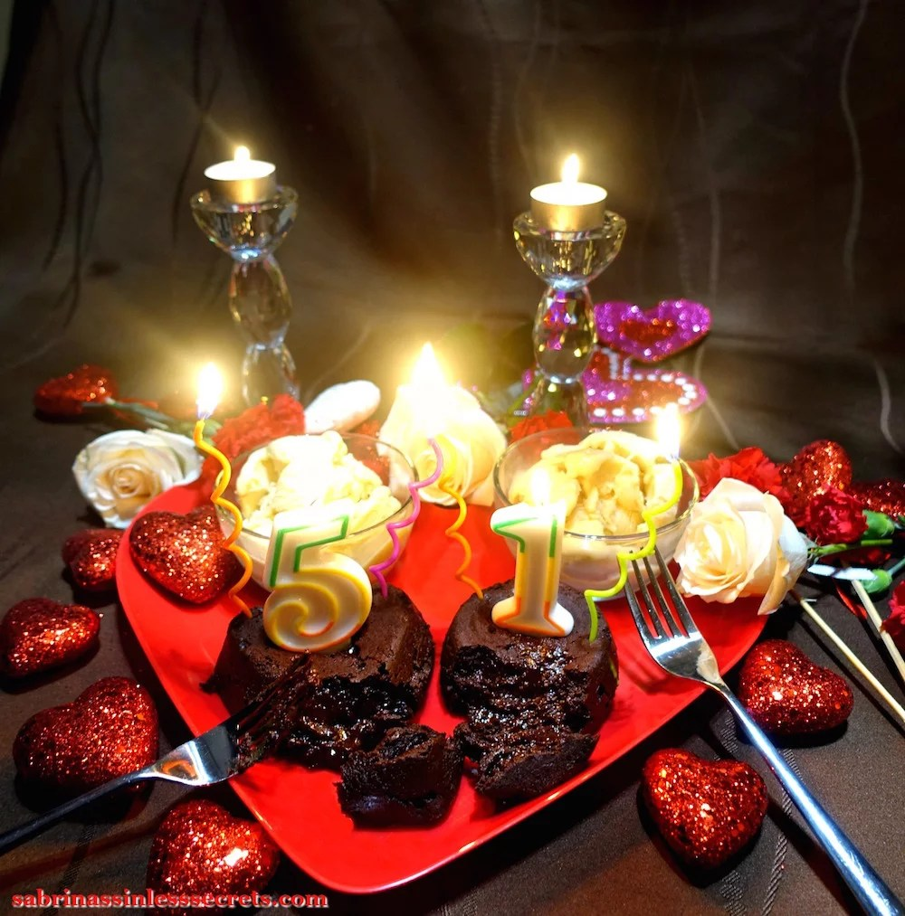 """Two Dark Chocolate Paleo Lava Cakes for Two with multicolored, lit """"5"""" and """"1"""" birthday candles atop them with two sides of Creamy Vanilla Bean Paleo Ice Cream, and two forks resting atop a red heart-shaped plate, with white roses, red carnations, red glittery hearts, and two crystal candle holders with white tea lights lit in the background."""