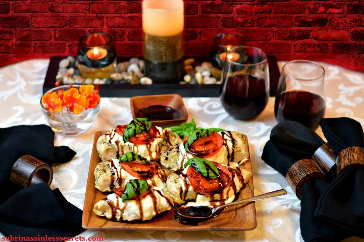 five homemade Chicken Caprese with Paleo Balsamic Reduction on a wood, square plate and a spoon full of balsamic reduction in front of them, along with black cloth napkins, two glasses or red wine, candles, and red and orange flowers in a clear bowl with a red brick background