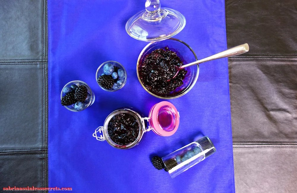 An overhead view of Paleo Black and Blueberry Jam in a glass bowl with a stainless steel spoon in it with a jar of more jam next to it, with shots of fresh blueberries and blackberries in them sitting on a blue placemat