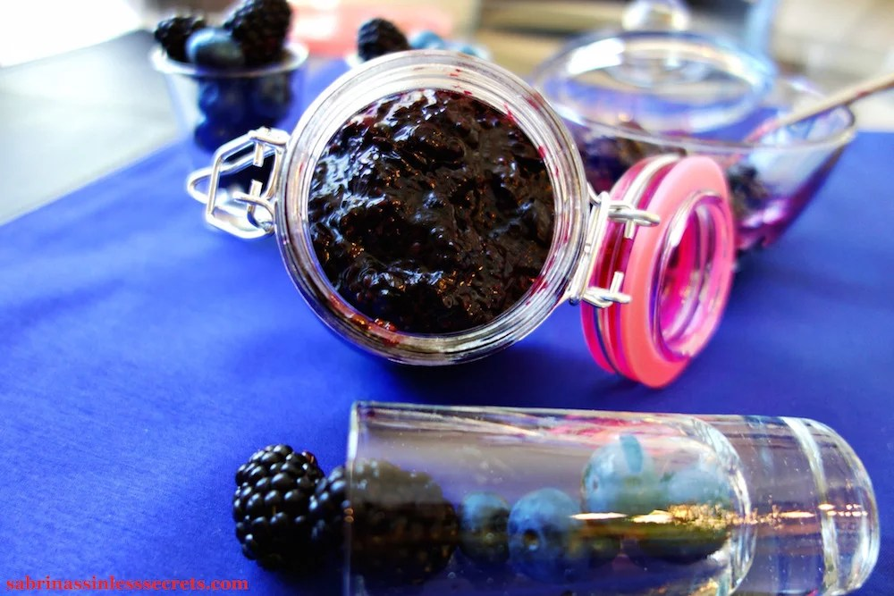 Paleo Black and Blueberry Jam in an opened airtight jar on it's side, resting on a blue placemat with shots of fresh blueberries and blackberries around it
