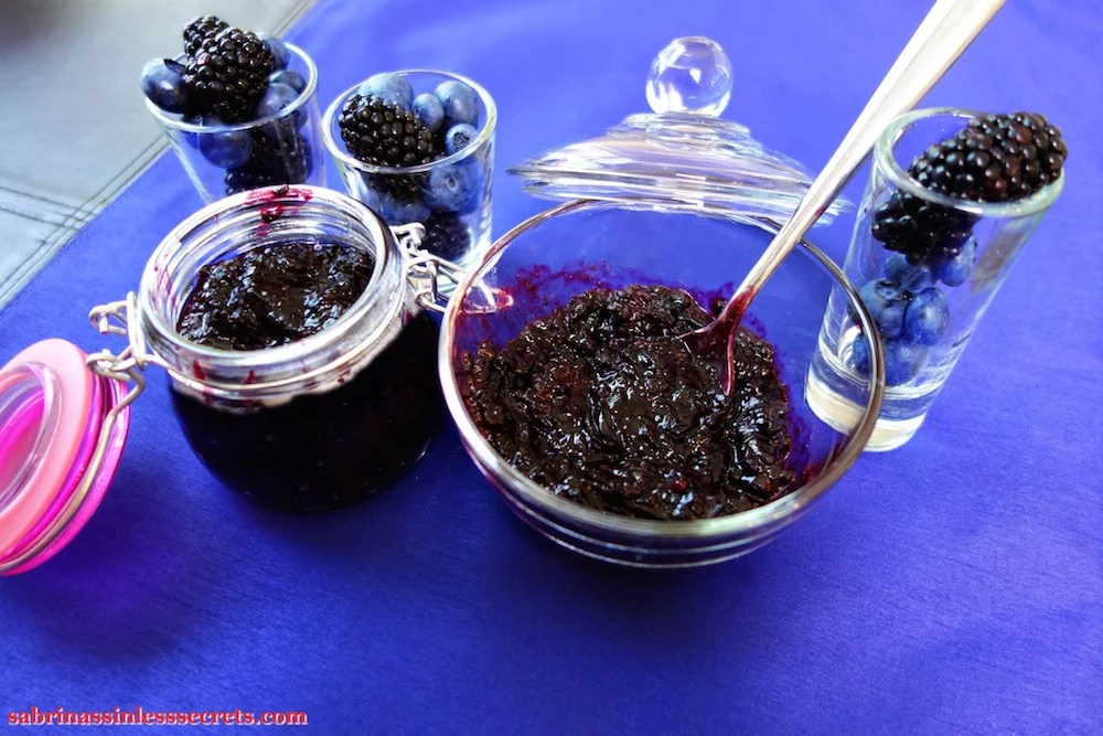 Paleo Black and Blueberry Jam in a glass bowl with a stainless steel spoon in it with a jar of more jam next to it, with shots of fresh blueberries and blackberries in them sitting on a blue placemat