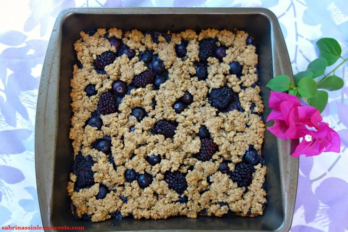Black & Blueberry Gluten-Free Crumble Bars fresh out of the oven in a 9x9 inch pan, resting on a floral lavender and light blue tablecloth with a fuchsia flower