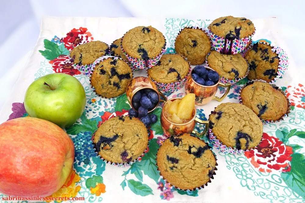 An arrangement of homemade Apple Blueberry Paleo Muffins on a colorful floral placement with two petite copper mugs full of blueberries and another one full of homemade Paleo chunky applesauce, also joined by one granny smith apple and one honey crisp apple