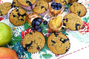 The top view of homemade Apple Blueberry Paleo Muffins joined by three petite copper mugs, two filled with fresh blueberries and other, homemade Paleo applesauce