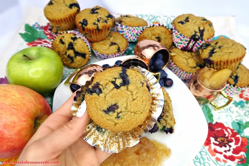 A hand holding a homemade Apple Blueberry Paleo Muffin with the wrapped half peeled off the sides and more muffins in the background, stacked and leaning on one another