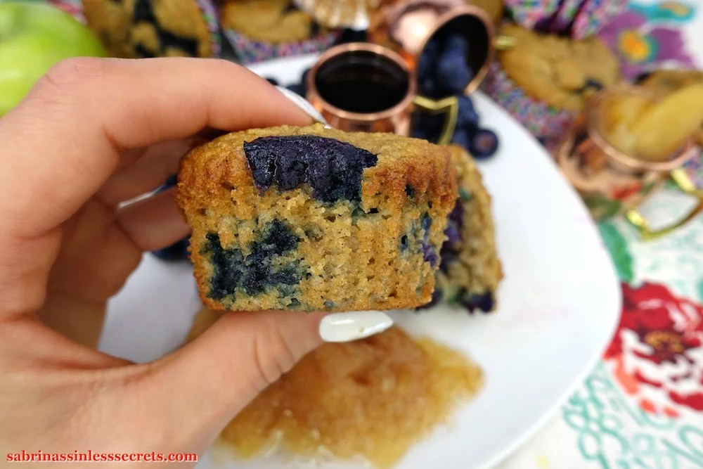 A hand holding an Apple Blueberry Paleo Muffin, showing the side view of bits of blueberries with a white plate in the background holding more muffins