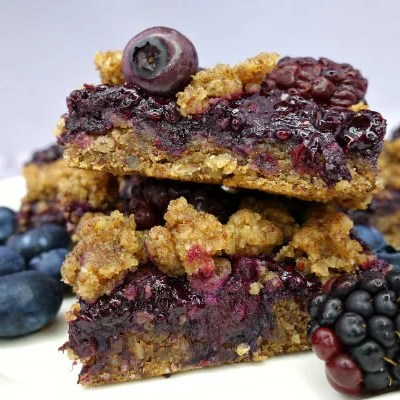 A stack of Black & Blueberry Gluten-Free Crumble Bars on a white plate with fresh blueberries and blackberries around them