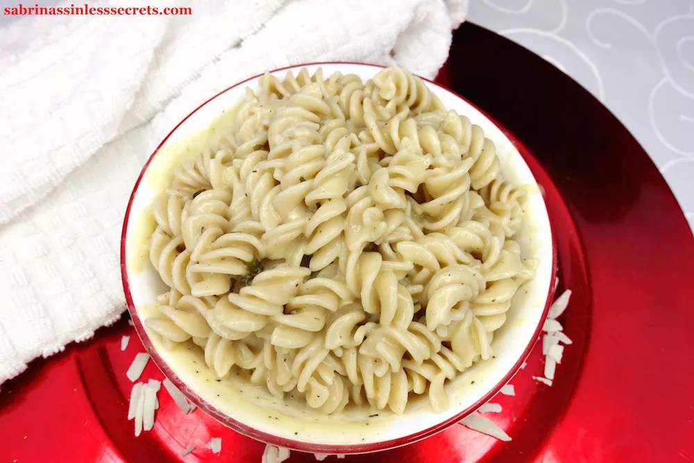 Homemade Sinless & Skinny Alfredo Sauce with gluten-free spiral pasta in a white bowl with red trim on a red charger, scattered with freshly shredded parmesan cheese, and a white towel around the bowl
