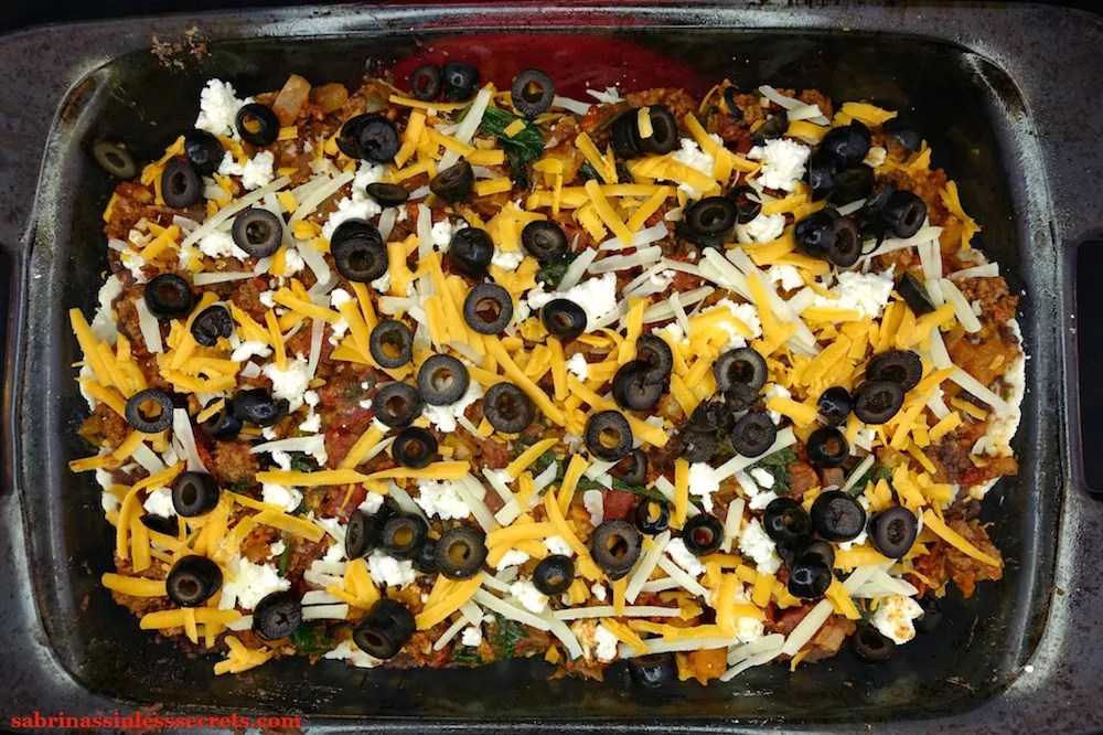 "Sliced black olives, shredded cheddar, Parmesan, and mozzarella cheese over A beef and vegetable mixture over ""refried"" black beans, cheddar, Parmesan, and mozzarella cheese, and Easy Paleo Tortillas in a glass 9x13-inch pyrex baking dish"