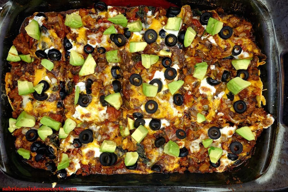 A homemade Gluten-Free Healthy Mexican Casserole topped with fresh, diced avocado in a glass 9 x 13 inch pyrex baking dish right out of the oven