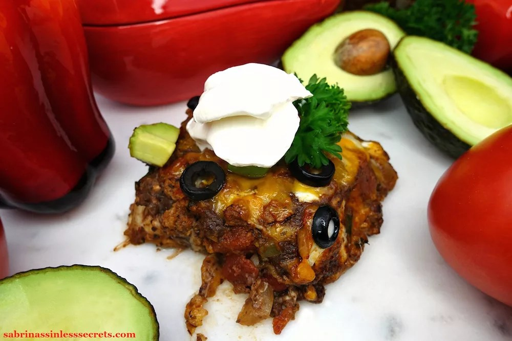 A serving square of homemade Gluten-Free Healthy Mexican Casserole, garnished with fresh parsley, sliced back olive, diced avocado, and a dollop of sour cream, with cut open avocados, a glass red chili pepper bowl, and tomatoes on the vine surrounding it