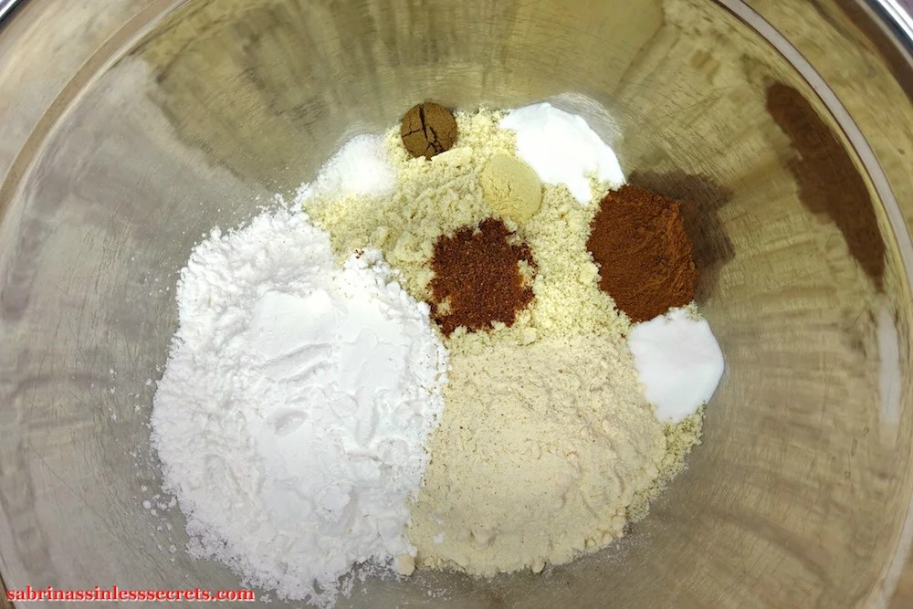 The dry ingredients for Paleo Carrot Cake with Paleo Vanilla Bean Cream Frosting in a large stainless steel mixing bowl