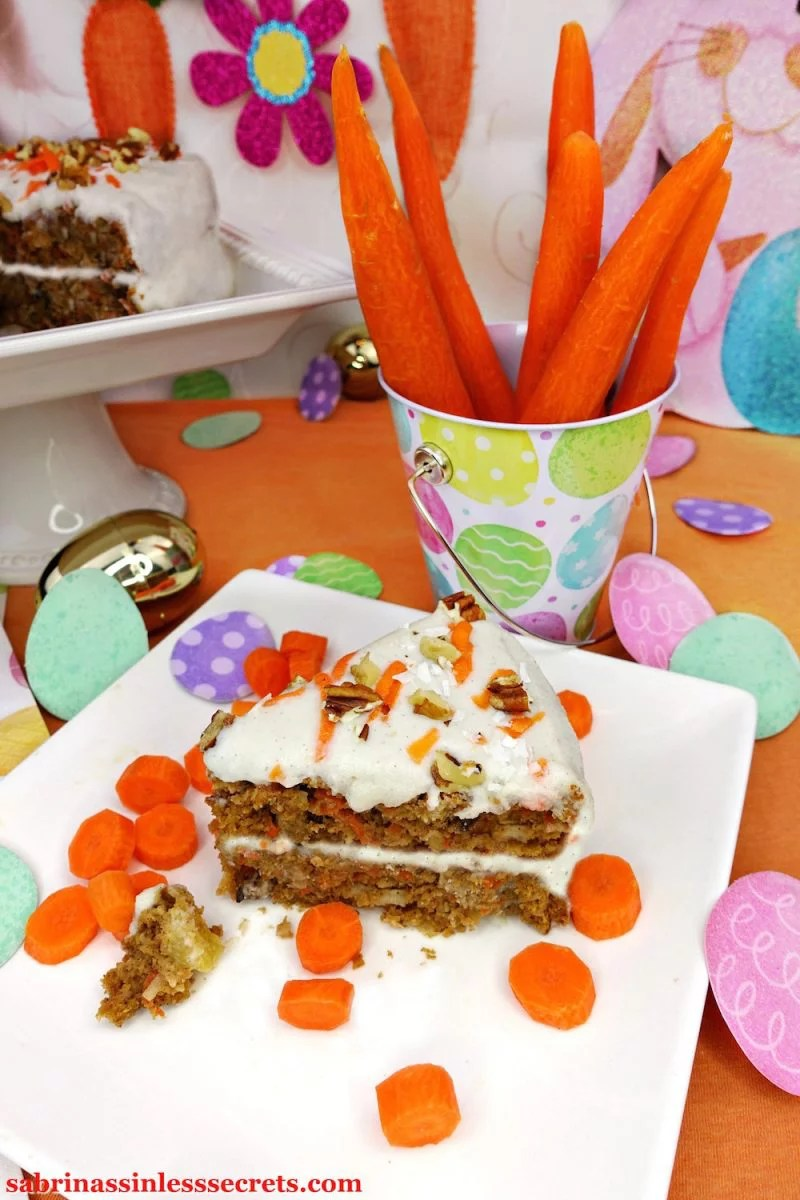 A piece of homemade Paleo Carrot Cake with Paleo Vanilla Bean Cream Frosting on a white plate with fresh slices of carrot and an Easter cup full of peeled carrots and glittery Easter eggs in the orange background