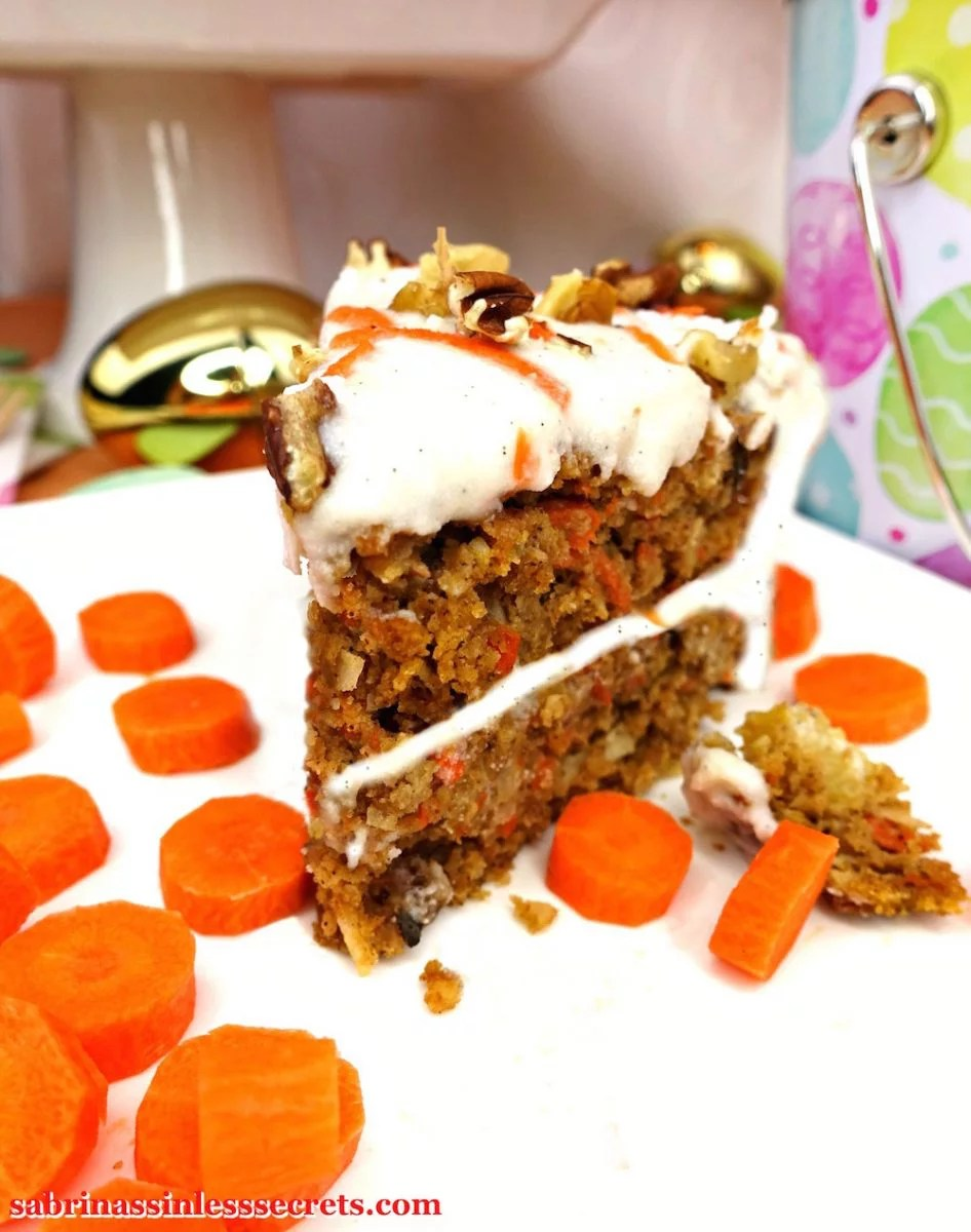 A piece of homemade Paleo Carrot Cake with Paleo Vanilla Bean Cream Frosting from the front on a white plate with slices of fresh carrot surround it and Easter eggs in the background