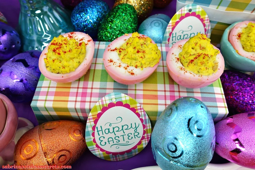 Pink & Paleo Deviled Eggs on a pastel plaid box with sparkly Easter eggs around them