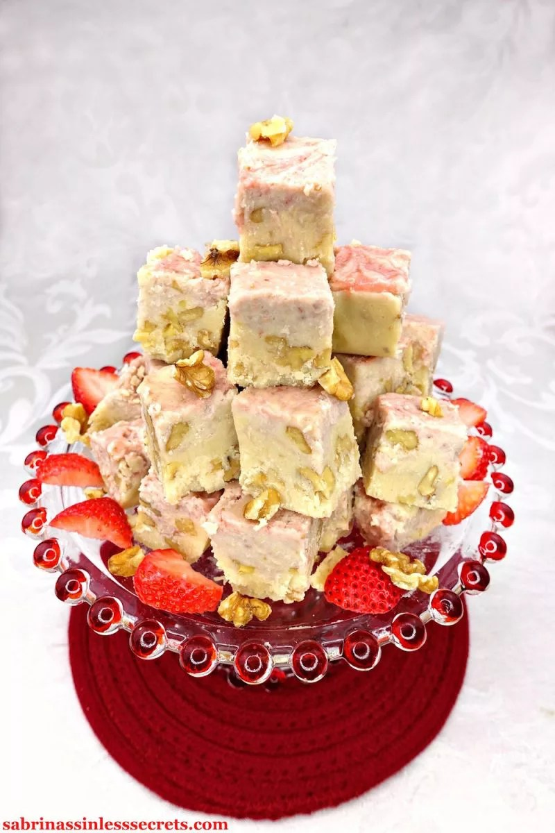 A pyramid of Paleo and Vegan Strawberry Swirl White Chocolate Walnut Fudge, topped with fresh walnuts and strawberry slices, on a clear glass platter with red balls along the perimeter, sitting on a red placemat on a white damask background