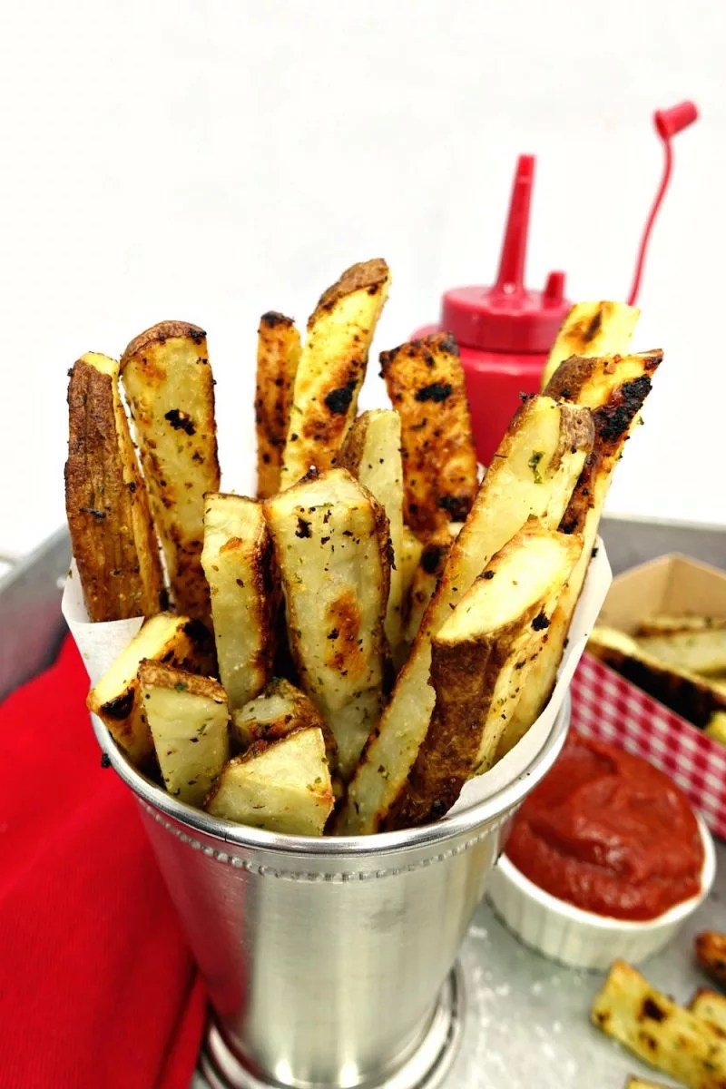 A stainless steel cup full sprouting with Seasoned Oven Baked Crispy French Fries with a red cloth napkin on the side of it, along with a small white side cup of homemade Quick and Easy Paleo Ketchup and more Seasoned Oven Baked Crispy French Fries