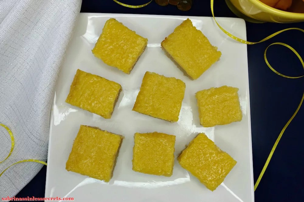 Homemade Paleo Lemon Bars with a Shortbread Crust scattered on a white, square plate with a sparkly, white cloth napkin on the side of it, along with yellow with white dotted ribbon