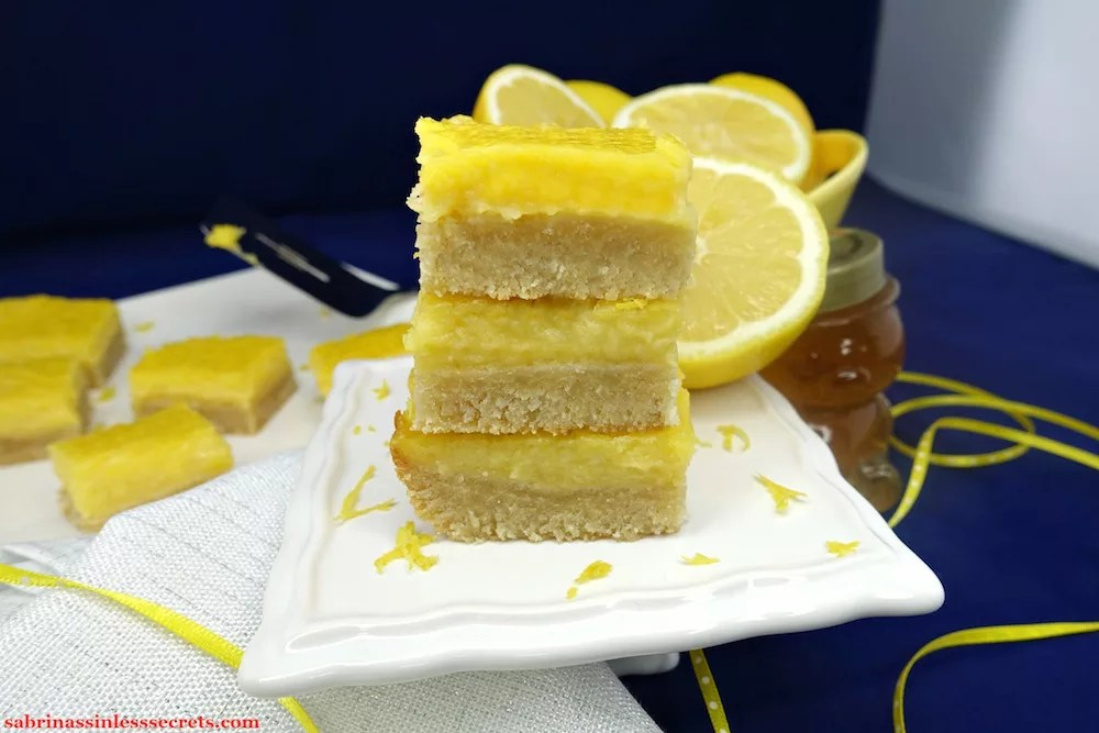 A stack of three homemade Paleo Lemon Bars with a Shortbread Crust with additional Paleo Lemon Bars with a Shortbread Crust on a white plate in the background with a pie server, in addition to half-sliced lemons, a honey bear, a white, sparkly cloth napkin, and yellow with white dotted ribbon in the background