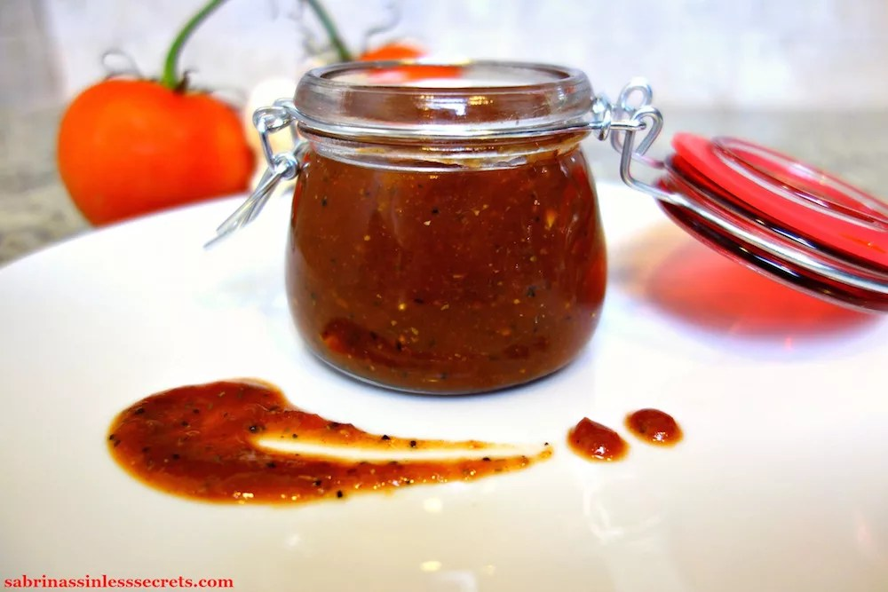 Easy Paleo BBQ Sauce in a small jar with a red latch lid on a white plate with a BBQ design in front of it and whole tomatoes and garlic in the background