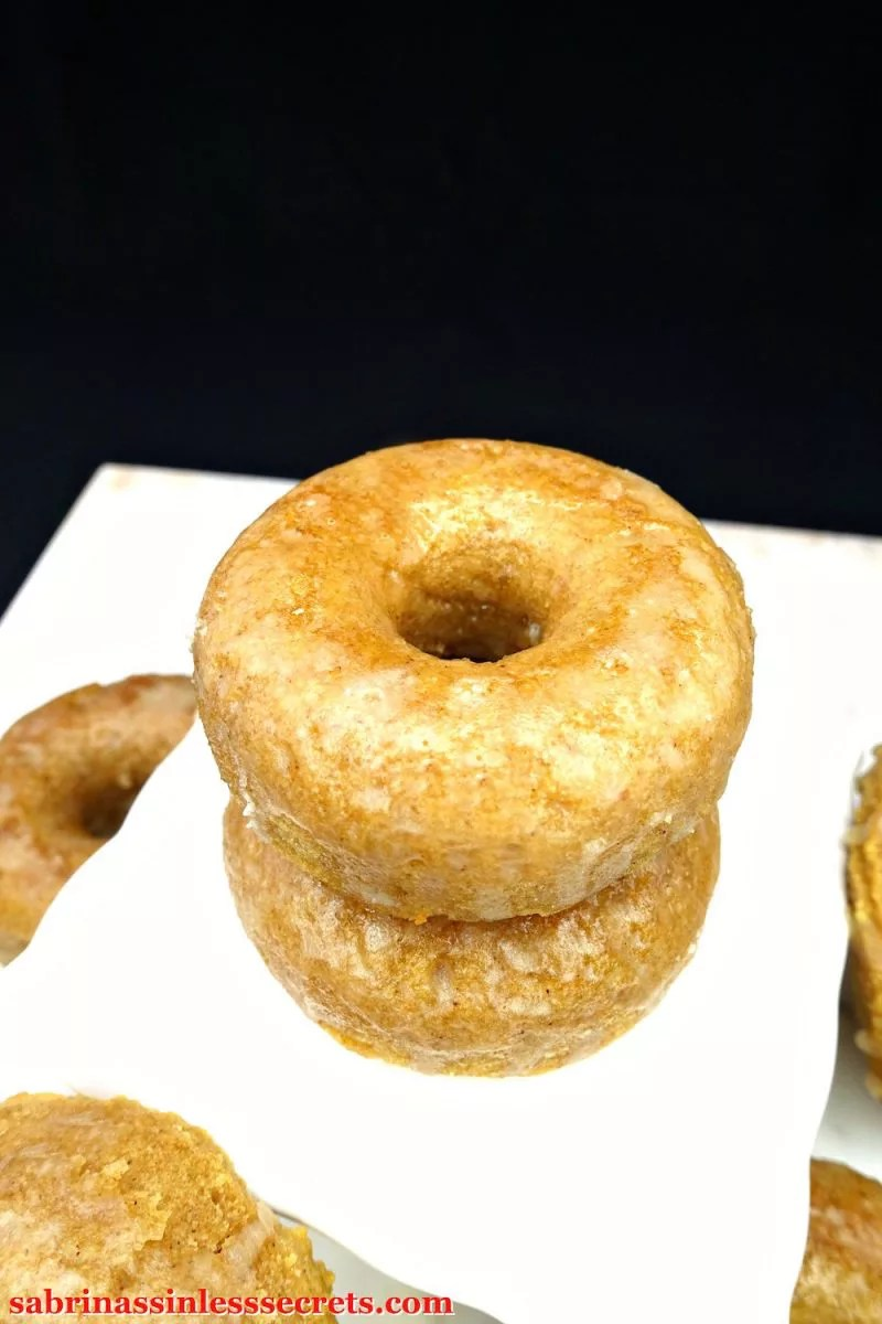 A double stack of Paleo Maple Glazed Baked Donuts on a white serving platter
