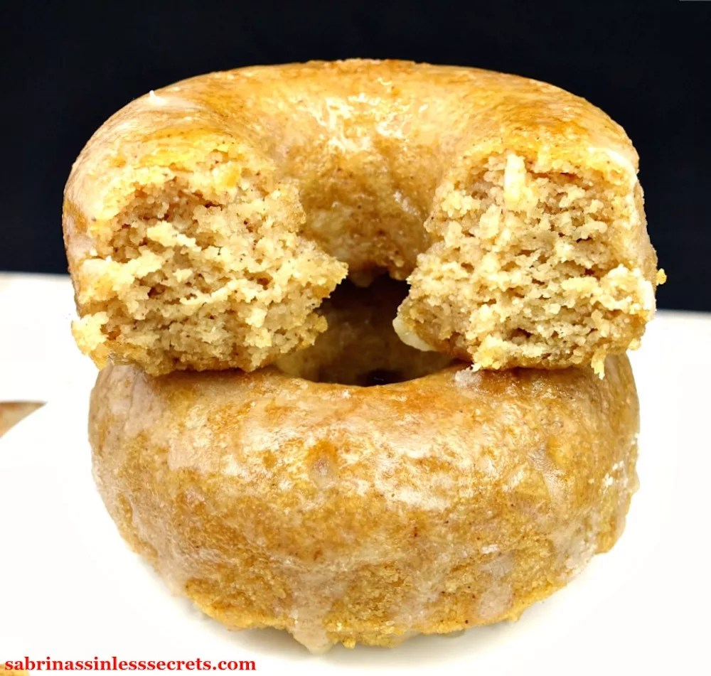 A double stack of Two Paleo Maple Glazed Baked Donuts stacked on a square, white serving platter on top of a white marble slab with more Paleo Maple Glazed Baked Donuts around them with the top one bitten in half on a white background