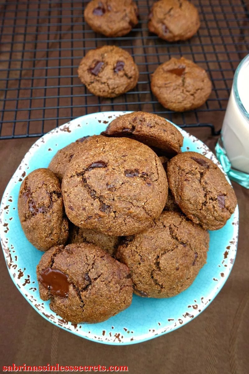 A distressed turquoise and brown bowl full of Double Dark Chocolate Chunk Paleo Brownie Cookies with more cookies on a cooling rack in the background