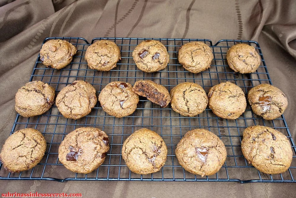 Double Dark Chocolate Chunk Paleo Brownie Cookies on a cooling rack, the center one half eaten